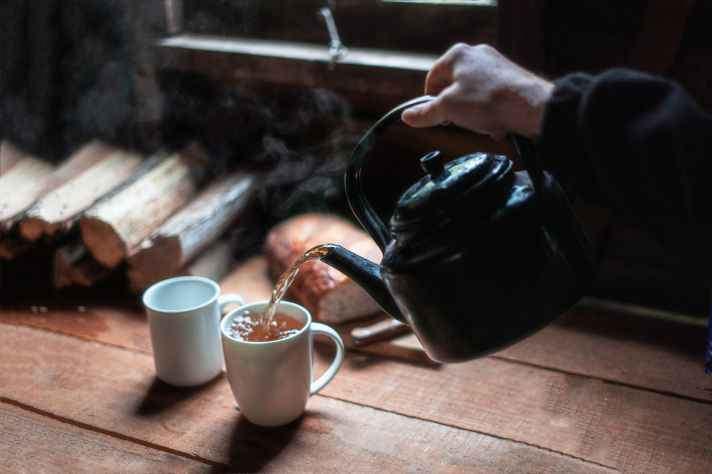photo of person pouring hot beverage on mug